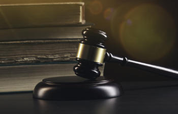 Open law book with a wooden judges gavel on table