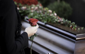 a woman with a rose stands by the coffin